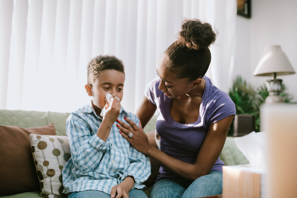 A boy blows his nose into a tissue, his mother comforting him during his illness.