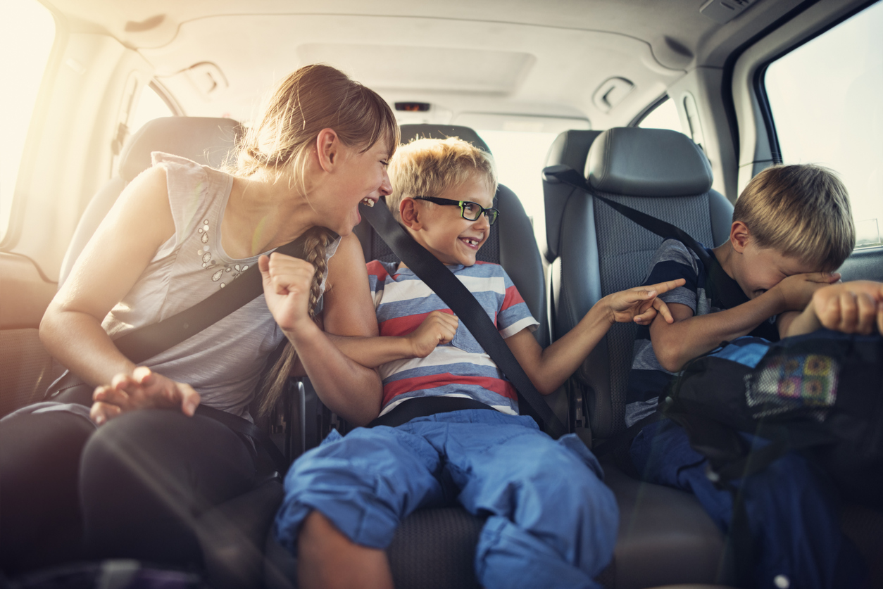Three kids laughing in car on a road trip.