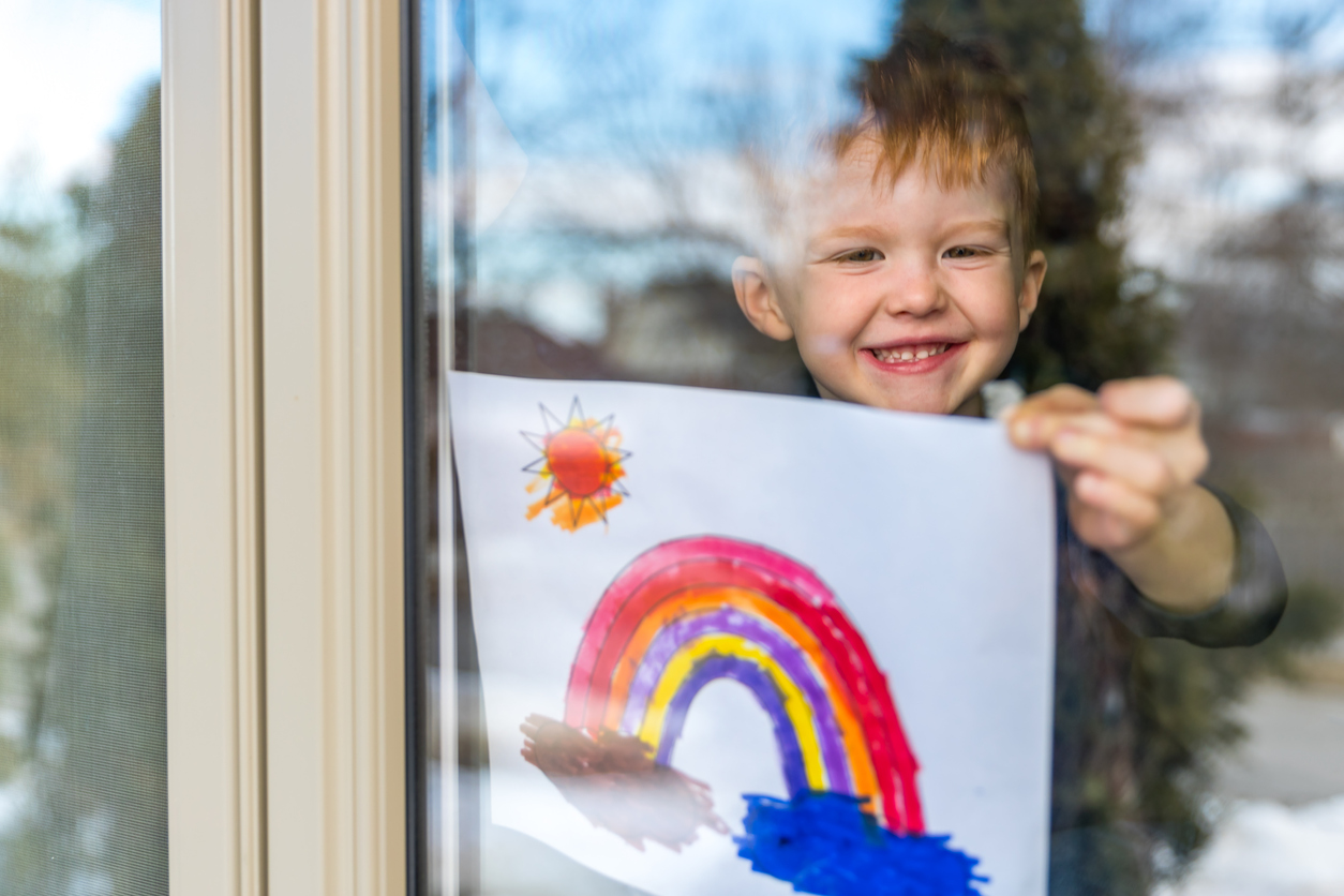 coronavirus kid holding rainbow picture up inside window