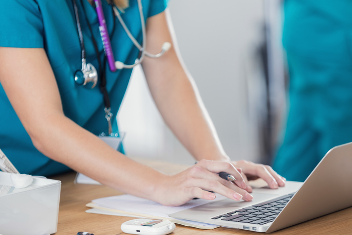 nurse uses laptop in hospital or doctor's office.