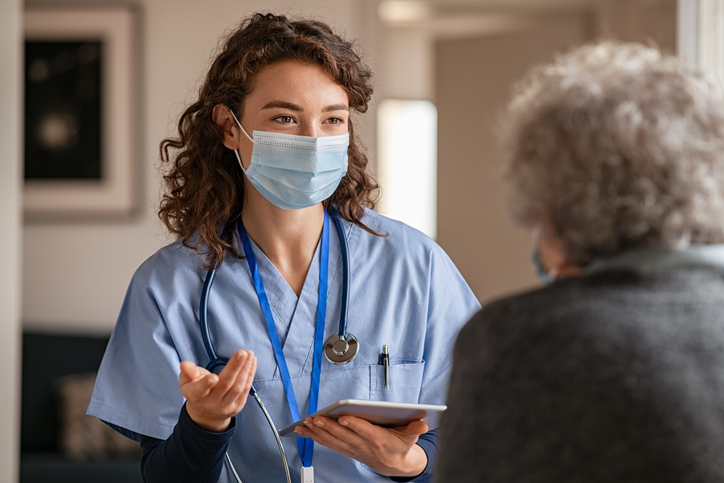Young doctor visits senior woman with surgical mask