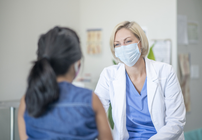 7 year old female patient speaking with her paediatrician in a doctors office, both are wearing masks due to the new COVID-19 regulations and to avoid the transfer of germs.